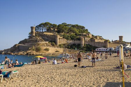 Beach under the castle in Tossa de Mar. People on the seafront near the walls of the old city. The historic city and the castle tower of La Vila Vella. A beautiful Catalan town on the Costa Brava