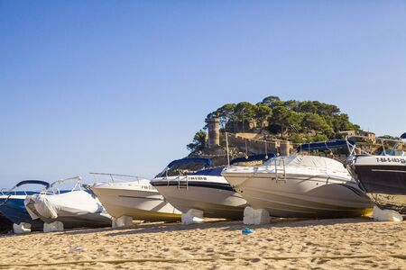 Beach under the castle in Tossa de Mar. Boats on the seafront near the walls of the old city. The historic city and the castle tower of La Vila Vella. A beautiful Catalan town on the Costa Brava Editorial