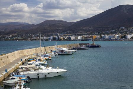 The harbor wharf in Hersonissos, Crete. Port with fishing boats and sailing boats on the Greek island. Publikacyjne