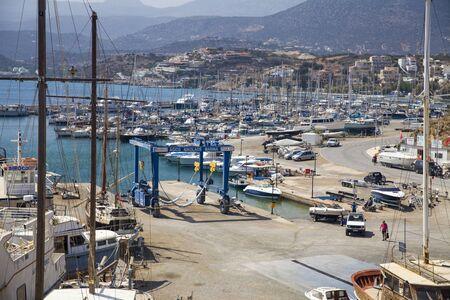 Agios Nikolaos, Crete  Greece - September 27, 2018: Port town of Agios Nikolaos. Water jetty off the coast of the city. Harbor with ships, moored boats, yachts and ships. Sajtókép