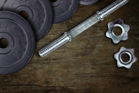 Dumbells and weights on the wooden floor. Fastening screws and barbells.