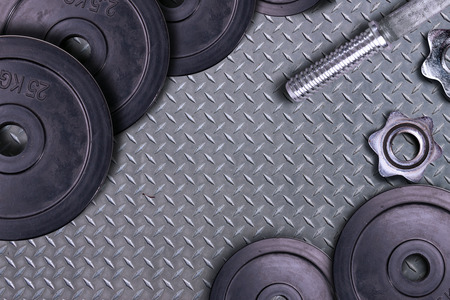 Dumbbells on carbon background. Dumbbells and weights are lying on the floor in the gym. Barbell set and gym equipment. Metal loads in the fitness club. Reklamní fotografie