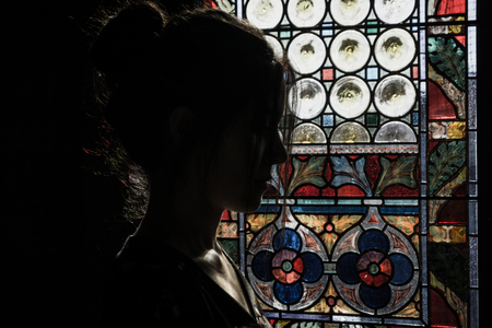 Girl looking at the colorful of windows of an old castle Stockfoto