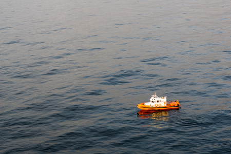 Smalll orange emergency response boat floating around an offshore oil field during sunset