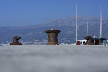 Rusty mooring bollards on a dock during sunny day.
