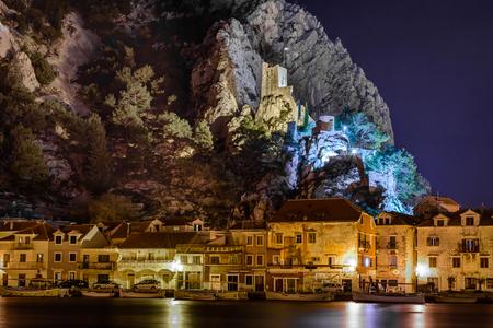 オミシュ、クロアチアの町の夜の町並み。Omis はクロアチアのアドリア海の町です。この古い観光都市のウォーター フロント夜景写真はタワー Mirabel