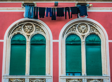 simetric: Architecture details of square Prokurative in town of Split with traditional way of drying clothes on rope between two windows, Croatia.