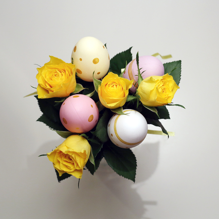 A bouquet made of yellow roses and colorful easter eggs