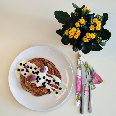 Delicious pancakes served with yoghurt and berries. Yellow flowers on the background.