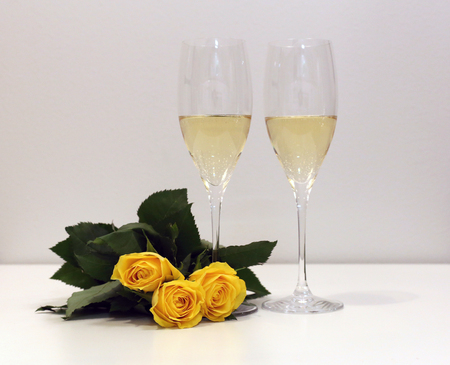 Two glasses of champagne  sparkling wine with some yellow roses