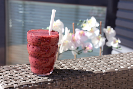 A glass of homemade healthy berry smoothie with pretty flowers on the background