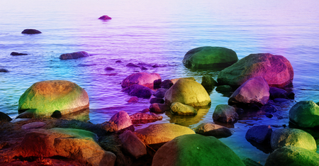 Colorful, magical fantasy themed fairytale-like landscape of rocks in the sea. This beautiful sea view is tuned with some amazing rainbow colors to make it fairytale-like and a bit mystic.
