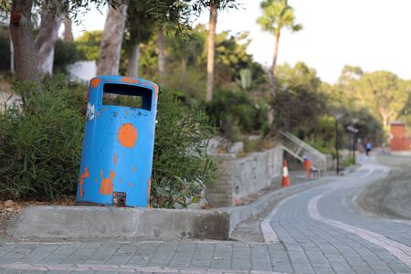 Blue trashcan and bench located near the beaches of Cyprus near Limassol. In this photo there is also some palm trees. Color image during sunny and warm summer afternoon. No people. Stock Photo