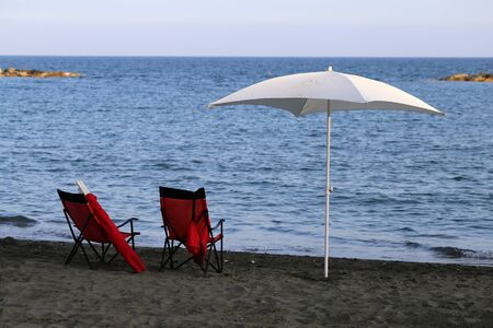 Two red deck chairs and a white umbrella on a beach with dark sand, Mediterranean sea in the background. Photographed during a sunny summer day in Cyprus. Luxurious life with good value for money.