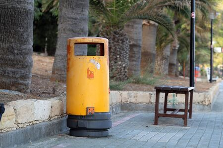 Yellow trashcan and bench located near the beaches of Cyprus near Limassol. In this photo there is also some palm trees. Color image during sunny and warm summer afternoon. No people. Stock Photo