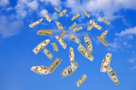 Symbol of wealth and success. Dollars falling from the blue sky. photo