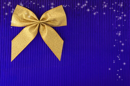 Gold bow on blue background.  photo