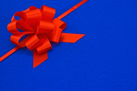 Gift red ribbon on blue background. Stock Photo - 16358185