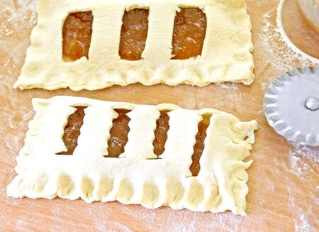 puff pastry: Homemade puff pastry with jam lay on a baking sheet.