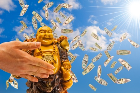 Feng shui. buddha against a blue sky with  falling  dollars.