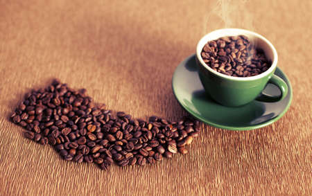 cup of hot coffee beans on textured background photo