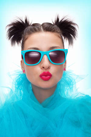 lips close up: pretty woman with blue eyeglasses is blowing a kiss