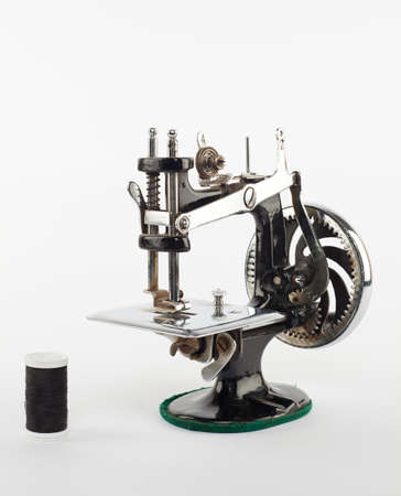 retro mini sewing machine with a thread isolated on white photo