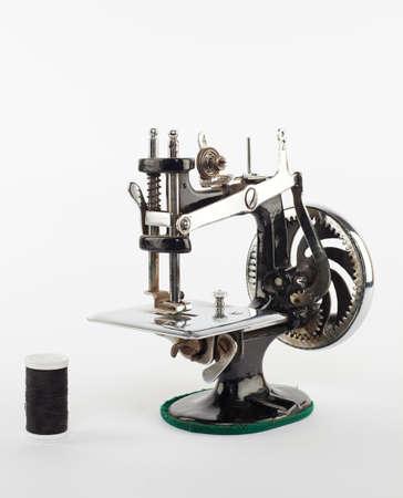 stitching machine: retro mini sewing machine with a thread isolated on white Stock Photo