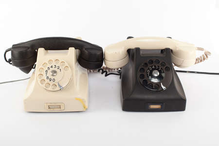 shifted: two telephones with their handsets shifted.isolated on white
