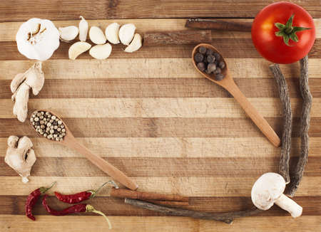 various vegetables and spices forming a frame on cutting board Stock Photo - 15860774