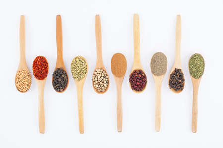 various spices on wooden spoons isolated on white background
