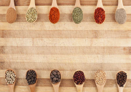 twelve spices on spoons on cutting board photo