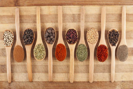 various spices on wooden spoons on cutting board photo