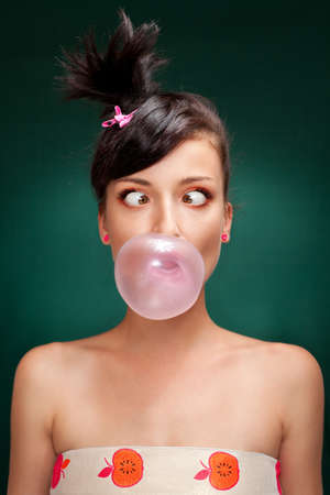 a beautiful brunette with squint eyed blowing a bubblegum on a green background  photo