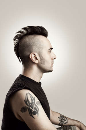 mohawk: profile picture of a tattooed man with mohawk style hair
