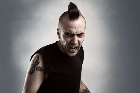 tattooed young man with mohawk style hair screaming photo