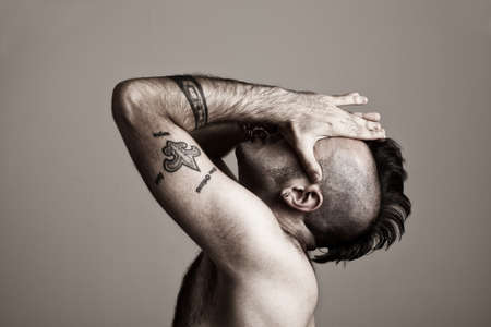 tattooed young man suffering.his hands on his face.