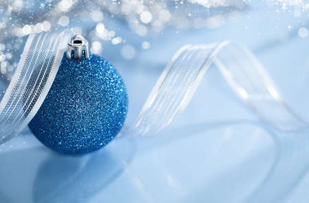 christmas background on a shiny and reflective surface with a blu ball and a ribbon