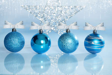 four blue christmas balls with ribbons on reflective surface