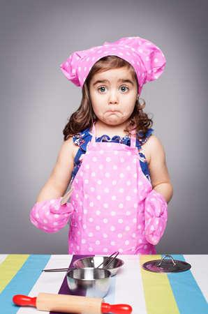 exitacion: cocinero confundido poco en ropa de color rosa cuchara de madera holdinga