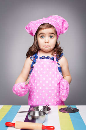 confused little cook in pink clothes holdinga wooden spoon