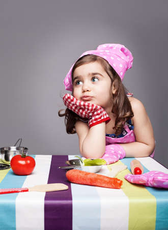 consider: little cute chef thinking about the meal she wants to prepare on grey background Stock Photo
