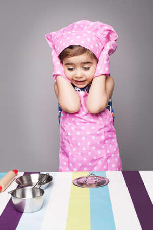 shocked face: little cute chef shocked when she saw empty pots on the table Stock Photo