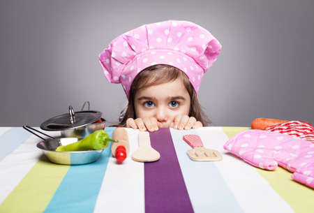 bowl game: very cute little girl dressed like a chef hidin behind the table and looking at camera