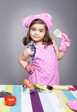 little cute girl with chef uniform posing like a proffesional model and looking at camera on grey background