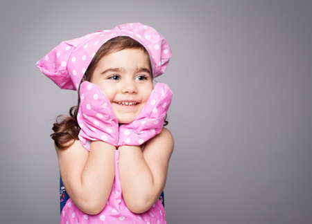 female chef: little cute chef wearing pink bib,hat and gloves smiling on grey background Stock Photo