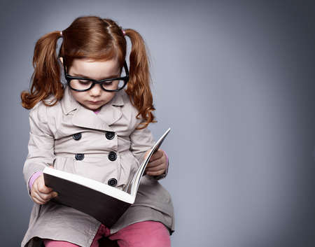 one story: little smart girl holding a book and reading it while sitting on a stool
