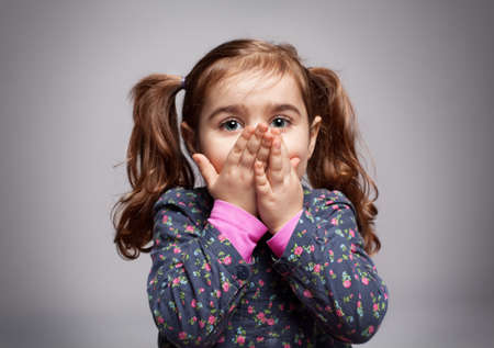 cute little girl trying to blow a kiss on grey background photo