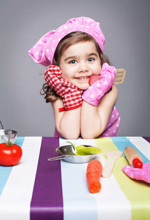 little cute chef holding wooden spoon with different pair of gloves looking at camera and smiling on gray background Stock Photo - 17639125