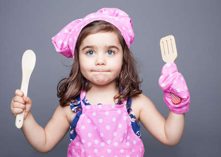 little cute chef with beautiful blue eyes  in pink clothes holding spoons in her hands